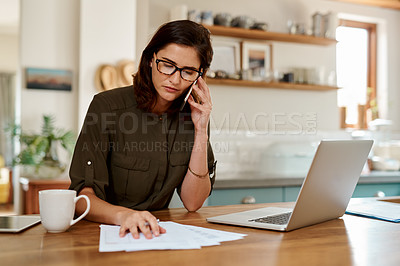 Buy stock photo Cropped shot of an attractive young woman making a phonecall while working from home