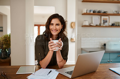 Buy stock photo Cropped portrait of an attractive young woman holding a cup of coffee while working from home