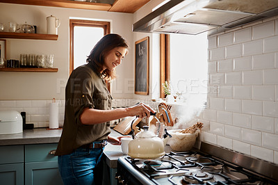 Buy stock photo Cropped shot of an attractive young woman making herself some tea in her kitchen at home