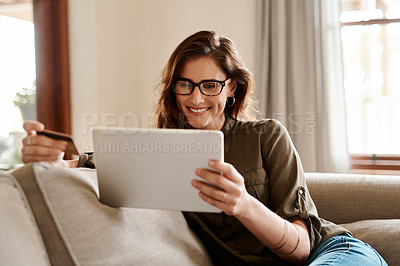 Buy stock photo Cropped shot of an attractive young woman using a digital tablet and a credit card to shop online while sitting in her living room at home