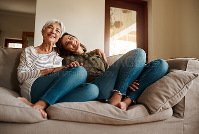 Buy stock photo Full length shot of an affectionate senior woman embracing her adult daughter while relaxing in their living room at home