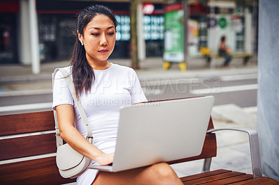 Buy stock photo Cropped shot of an attractive young woman wearing earphone and sitting on a street bench while using her laptop