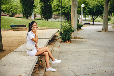 Buy stock photo Full length shot of an attractive young woman sitting in the park and talking on her cellphone during a vacation