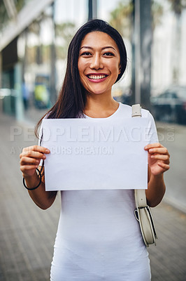 Buy stock photo Cropped portrait of an attractive young woman standing on the street and holding up a poster while sight-seeing in Spain