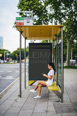 Buy stock photo Full length shot of an attractive young woman wearing earphones and using her cellphone while sitting in a bus stop