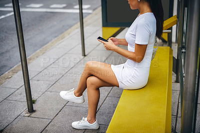 Buy stock photo Cropped shot of an unrecognizable woman sitting at a bus stop and using her cellphone during a vacation in Spain