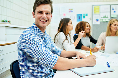 Buy stock photo Portrait of a handsome young designer taking down some notes during a meeting with colleagues at work