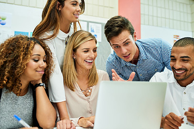 Buy stock photo Shot of a group of young designers working on a laptop together during their meeting at work