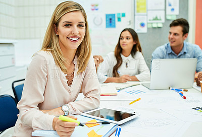 Buy stock photo Portrait of an attractive young designer taking down some notes during a meeting with colleagues at work
