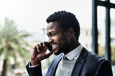 Buy stock photo Shot of a young businessman talking on a cellphone while standing outside an office