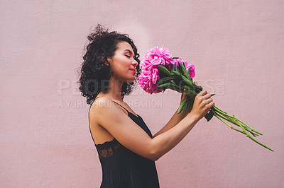 Buy stock photo Shot of an attractive young woman posing with a bouquet against a pink background