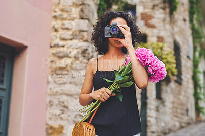 Buy stock photo Shot of a young woman taking pictures with her camera while exploring a city