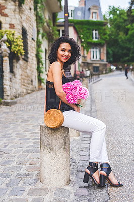 Buy stock photo Shot of an attractive young woman holding a bunch of flowers while out exploring a city