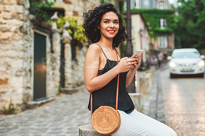 Buy stock photo Shot of an attractive young woman using her cellphone while out exploring a city
