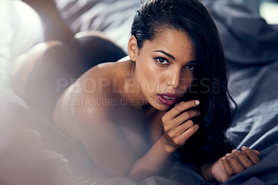 Buy stock photo Shot of a beautiful young woman lying on her bed in lingerie at home