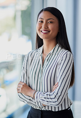 Buy stock photo Portrait of an attractive and happy young businesswoman posing with her arms folded inside her office