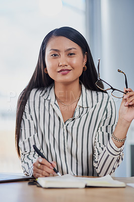 Buy stock photo Shot of an attractive young businesswoman writing notes in her journal while working inside her office