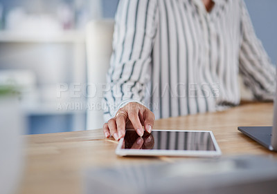 Buy stock photo Shot of an unrecognizable businesswoman using a digital tablet while working inside her office
