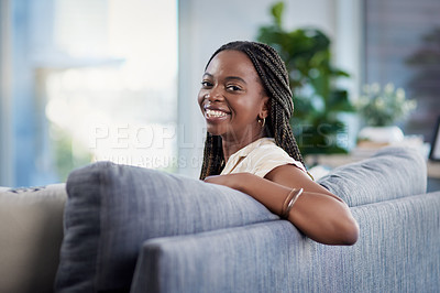 Buy stock photo Portrait of an attractive and happy young woman relaxing in her living at home