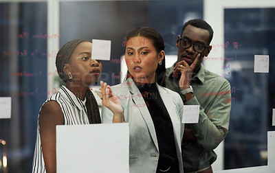 Buy stock photo Shot of three young businesspeople brainstorming with sticky notes on a glass wall inside a modern office