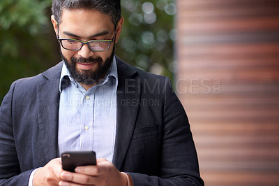Buy stock photo Shot of a mature businessman using a cellphone outdoors