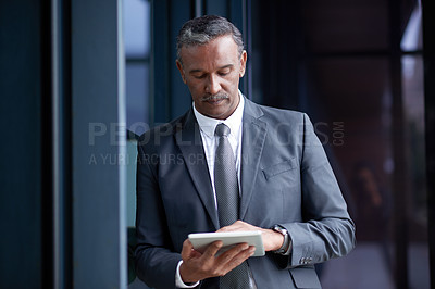 Buy stock photo Shot of a mature businessman using a digital tablet outside an office