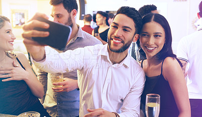 Buy stock photo Shot of a young man and woman taking a selfie together in a nightclub