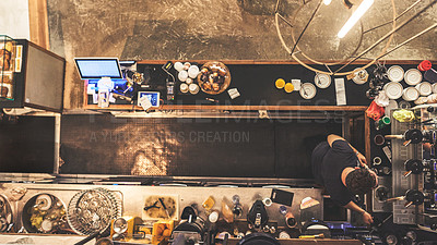 Buy stock photo High angle shot of an unrecognizable man working behind the counter making coffee inside of a cafe during the day