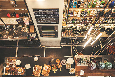 Buy stock photo High angle shot of fully stocked shelves behind a counter of a coffee shop during the day