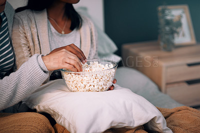 Buy stock photo Cropped shot of two unrecognizable women eating popcorn at home