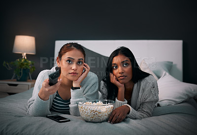 Buy stock photo Shot of two young women eating popcorn while watching a movie at home