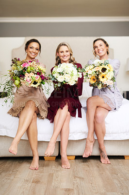 Buy stock photo Full length portrait of three beautiful young bridesmaids holding bouquets of flowers while sitting on a bed in their dressing room