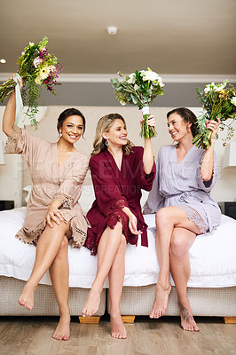 Buy stock photo Full length shot of three beautiful young bridesmaids holding up bouquets of flowers while sitting on a bed in their dressing room