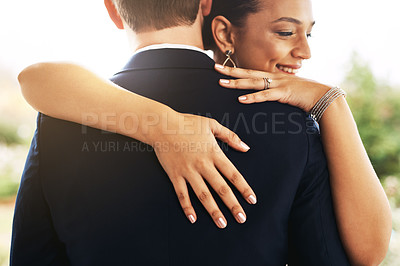 Buy stock photo Shot of a beautiful young bride hugging and embracing her groom outdoors on their wedding day