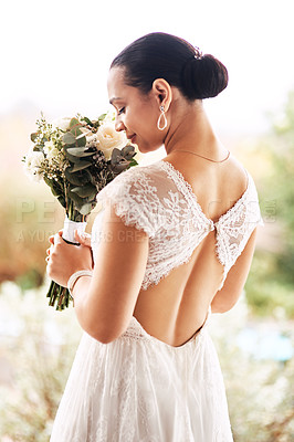 Buy stock photo Shot of a beautiful young bride smelling her bouquet of flowers outdoors on her wedding day