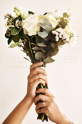 Buy stock photo Cropped shot of an unrecognizable bride holding a bouquet of flowers against a light background
