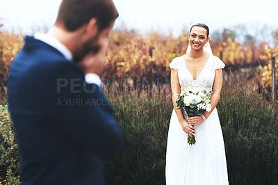 Buy stock photo Shot of a bridegroom crying while looking at his beautiful bride on their wedding day