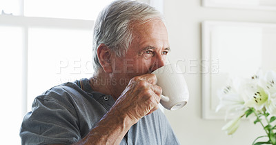 Buy stock photo Shot of a senior man having a cup of coffee at home