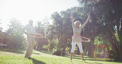 Buy stock photo Full length shot of an energetic senior couple playing with hula hoops in a park during the day