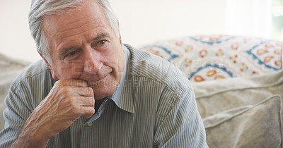 Buy stock photo Shot of a senior man looking on thoughtful while sitting on the sofa at home