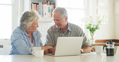Buy stock photo Shot of senior couple using a laptop and credit card together at home