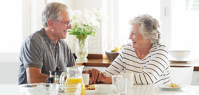 Buy stock photo Shot of a happy senior couple enjoying breakfast together at home
