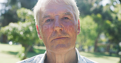 Buy stock photo Closeup portrait of a senior man looking serious while standing in a park during the day