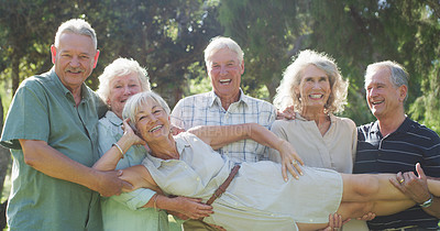 Buy stock photo Cropped shot of a group of senior friends carrying their female friend while enjoying a day at the park