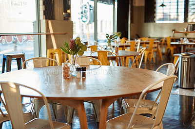 Buy stock photo Cropped shot of tables and chairs arranged in an empty coffee shop during the day