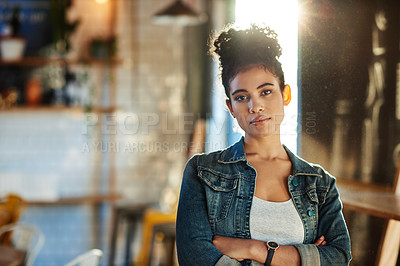 Buy stock photo Cropped shot of an attractive young businesswoman standing alone with her arms folded in her coffee shop
