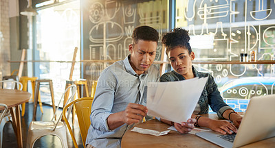 Buy stock photo Cropped shot of two young business colleagues using a laptop during a discussion over their financial paperwork in a cafe