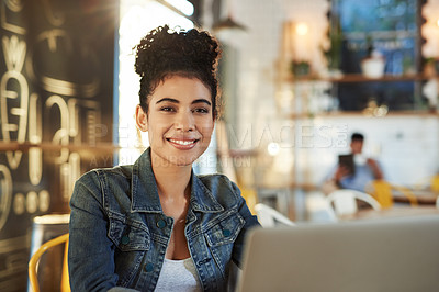 Buy stock photo Cropped shot of an attractive young cafe owner sitting in her coffee shop and using a laptop
