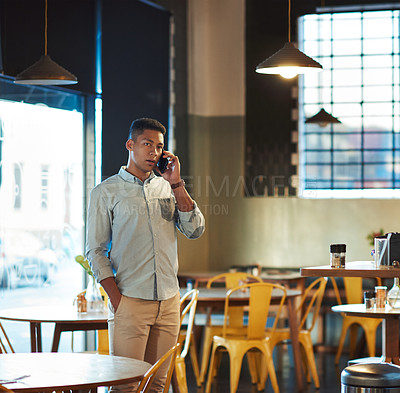 Buy stock photo Cropped shot of a handsome young man standing alone in a coffee shop and talking on his cellphone