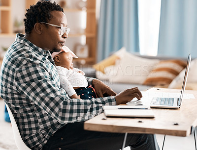 Buy stock photo Shot of a man using his laptop while sitting at home with his baby